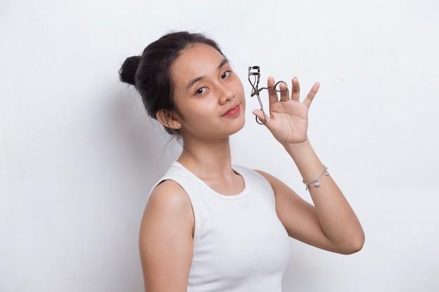 白い背景で隔離のまつげカーラーを持つ美しい若いアジアの女性