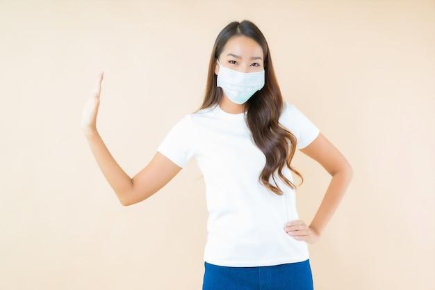 Bella giovane donna asiatica con maschera facciale fermandosi a mano
