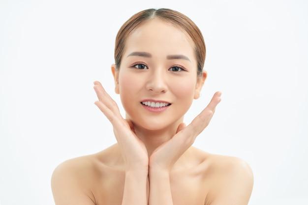 両手で彼女の顔に触れる新鮮なきれいな肌を持つ美しい若いアジアの女性。スパ、美容、美容。