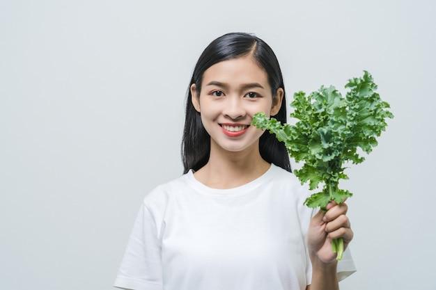 スタジオでケールの葉を持つ美しい若いアジアの女性。健康と美しい肌のための高ビタミンビーガンフード。