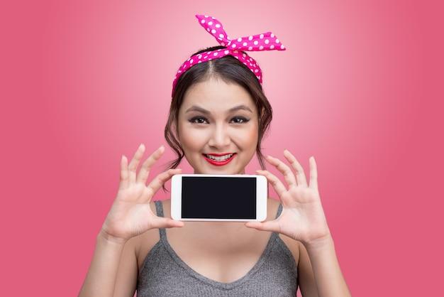 携帯電話でピンクの背景にピンナップメイクと髪型を持つ美しい若いアジアの女性