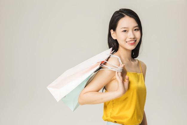 Красивая молодая азиатская женщина с изолированными сумками