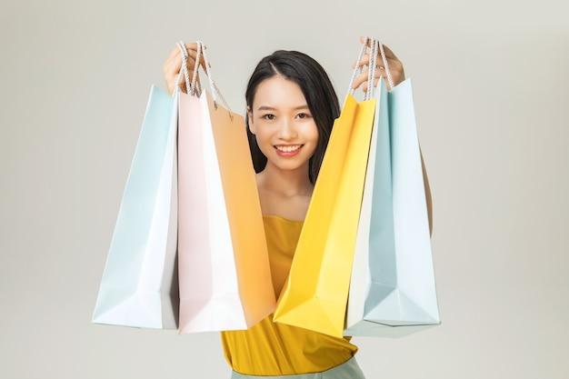分離された買い物袋を持つ美しい若いアジア女性