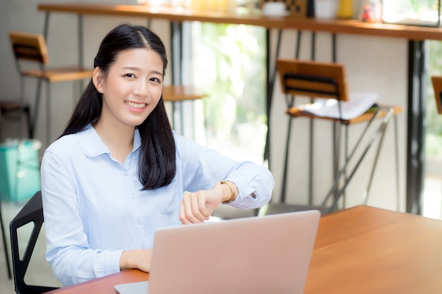 Beautiful young asian woman working on laptop in cafe looking on wristwatch.