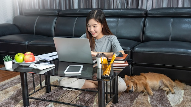Beautiful young asian woman working remotely from home and smiling while lying, has good relationships with with a funny assistant dog pet, home work pets concept.