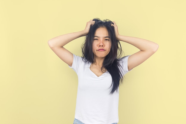 Beautiful young asian woman on yellow background