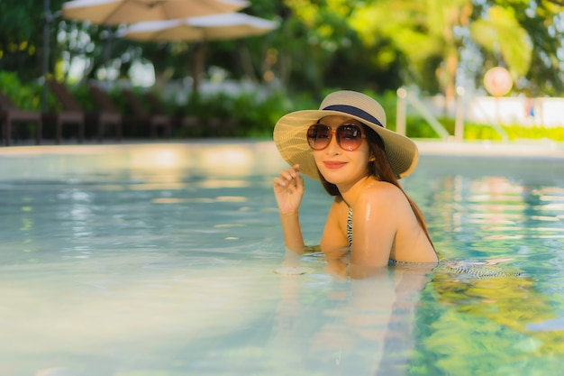 Beautiful young asian women happy smile relax around outdoor swimming pool in hotel resort for travel in holiday vacation