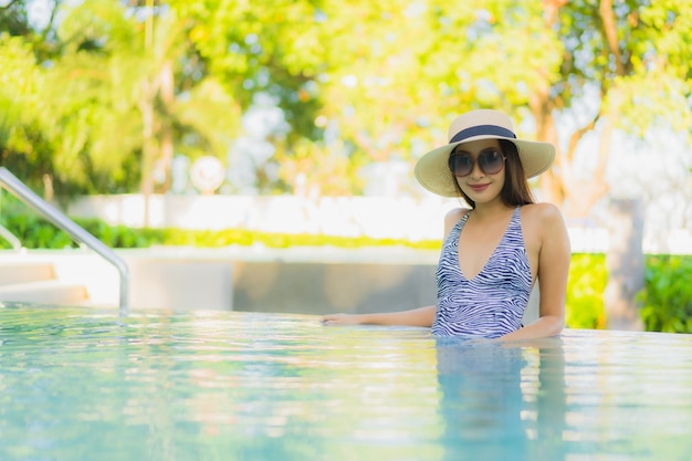 Beautiful young asian women happy smile relax around outdoor swimming pool in hotel resort