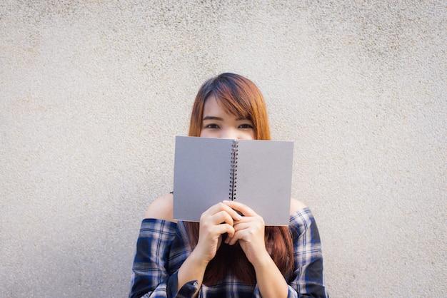 Bella giovane donna asiatica che si nasconde dietro un libro grigio sullo sfondo della parete di cemento. immagini di stile d'effetto vintage.