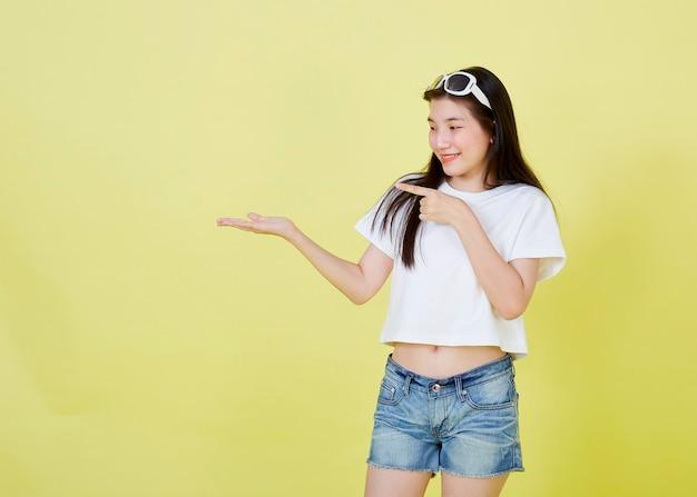 Красивые молодые азиатские женщины с очками на голове, указывая в сторону на желтом фоне