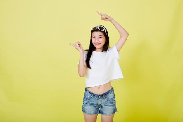 Красивые молодые азиатские женщины с очками на голове, указывая вверх на желтом фоне