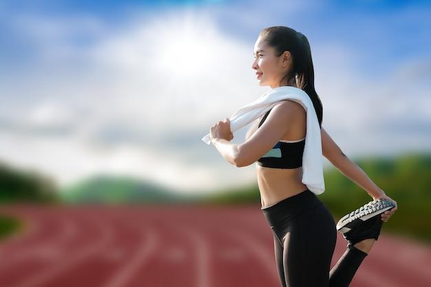 Красивые юные спортсменки разминаются перед беговой тренировкой на открытом стадионе.