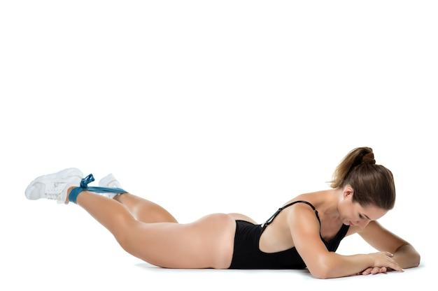 白い背景で隔離の弾性ゴムで筋力トレーニングを行う黒体の美しい若い運動少女