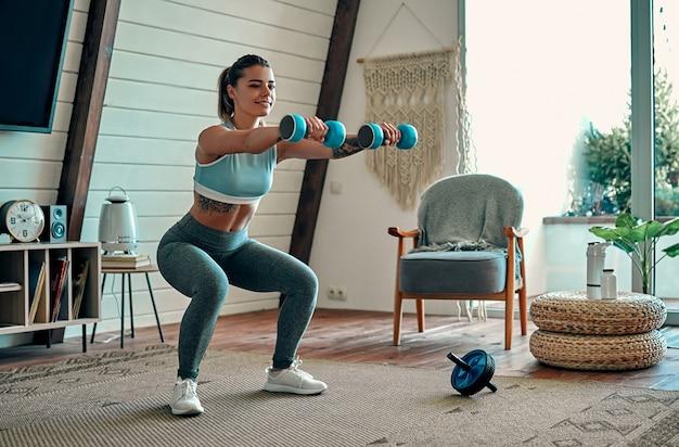 Красивая молодая спортивная девушка в леггинсах и топе приседает с гантелями дома. спорт, здоровый образ жизни.