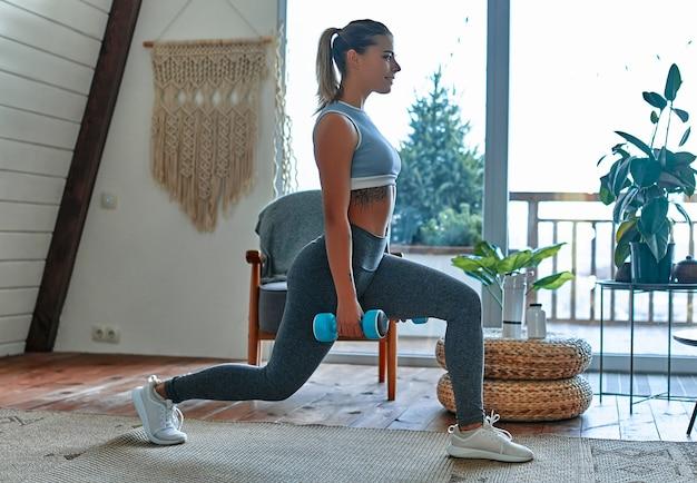Красивая молодая спортивная девушка в леггинсах и топе делает выпады с гантелями дома. спорт, здоровый образ жизни.