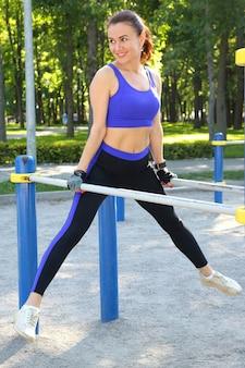 Красивая молодая спортивная женщина делает гимнастику на руках на баре