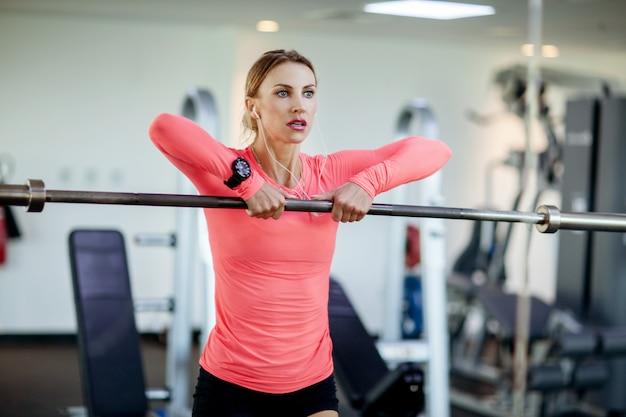 美しい若い運動女性はジムでトレーニングします。