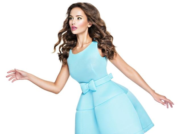 파란 드레스에 긴 머리를 가진 아름 다운 젊은 매력적인 여자. 매력적인 패션 모델 흰색 배경에 포즈입니다.