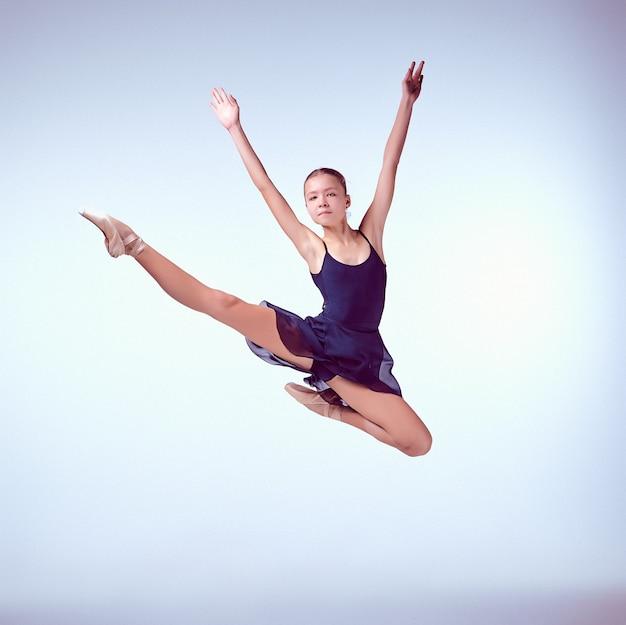 灰色の背景にジャンプする美しい若いバレエダンサー
