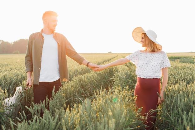 하얀 모자를 쓴 아름다운 젊고 아름다운 임산부는 저녁 산책을 하는 동안 들판에 남편의 손을 잡고 있습니다. 임신과 보살핌. 행복과 부드러움. 배려와 관심. 사랑 .