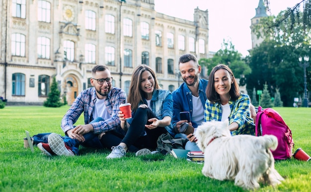 Beautiful young best friends with little funny dog on the lawn are having fun and relaxing