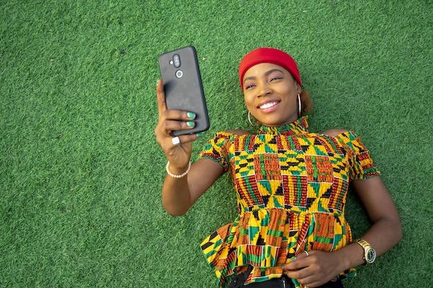 彼女の携帯電話を使用して公園の床に横たわっている美しい若い黒人女性