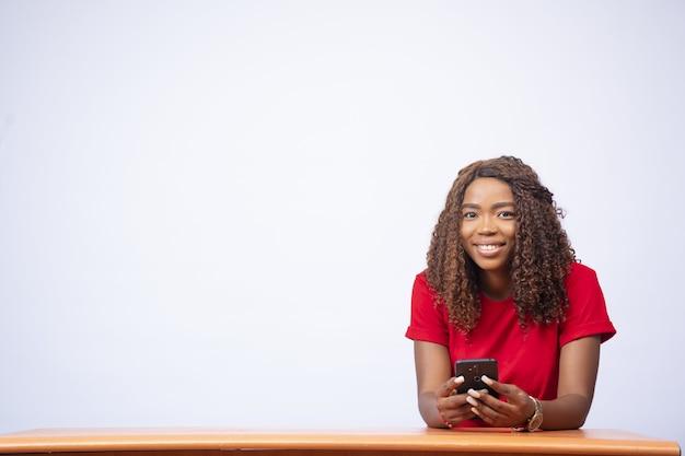 Красивая молодая темнокожая дама сидит за столом и разговаривает по телефону