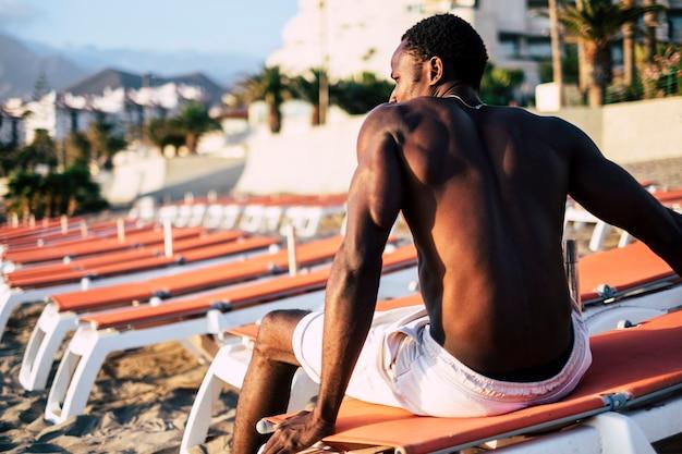 아름 다운 젊은 흑인 모델 남자는 해변 좌석에 앉아. 헬스장과 건강 식품으로 만든 인상적인 몸매와 근육, 야채와 다이어트. 완벽한 몸매를 얻기위한 멋진 라이프 스타일