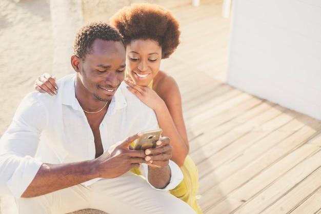 아름다운 젊은 흑인 피부 인종 다양한 커플이 인터넷에 연결된 현대적인 스마트 폰을 함께 사용하여 소셜 미디어를 확인하거나 뉴스를 읽거나 프라이드에게 연락합니다. 수천 년 동안 현대적인 장치 사용