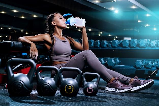 Красивая молодая черная спортсменка в тренажерном зале выполняет тренировку