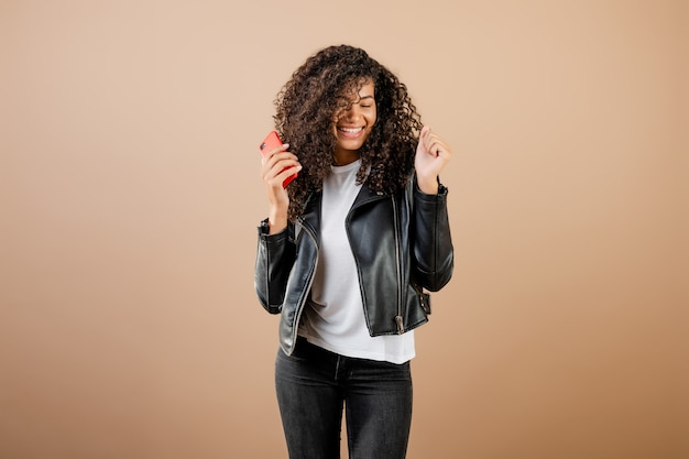 Beautiful young black woman dancing and singing with phone in hand isolated over brown
