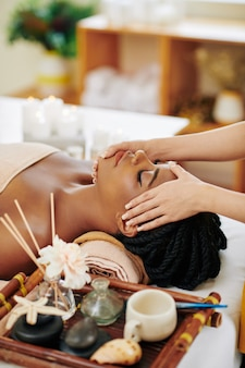 Beautiful young black woman enjoying face and head massage in spa salon when lying on bed next to tray with aroma oils