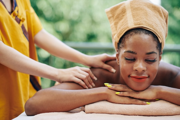 Beautiful young black woman getting back and shoulders massage in spa salon and closing eyes from enjoyment