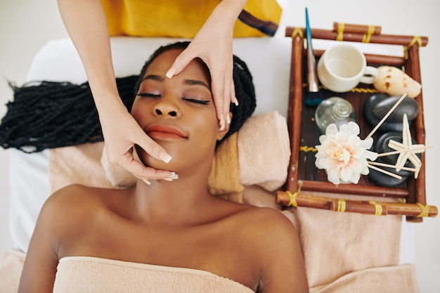 Beautiful young black woman getting lifting face massage in spa salon, view from above