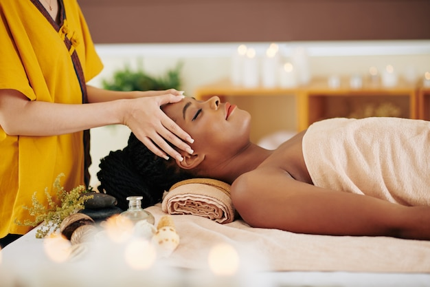 Beautiful young black woman getting rejuvenating face massage with oils in spa salon