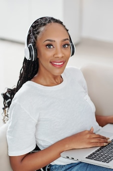 Beautiful young black woman in headphones programming on laptop at home