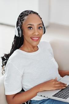 집에서 노트북에 프로그래밍 헤드폰에서 아름 다운 젊은 흑인 여성