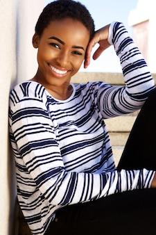 屋外で笑顔美しい若い黒人の女性