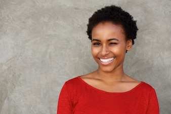 Beautiful young black woman winking eye and smiling