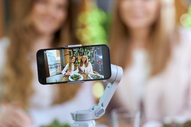 전화 카메라에 포즈를 취하는 아름 다운 젊은 블로거 여자
