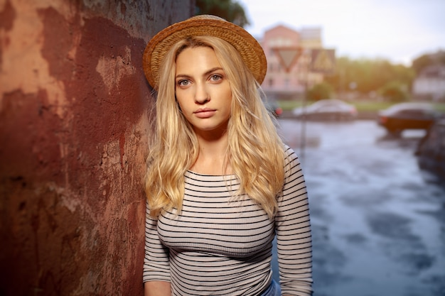 A beautiful young blond female student in a straw hat