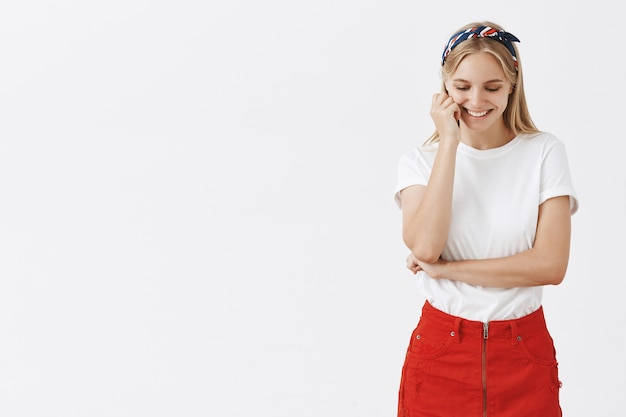 Красивая молодая блондинка позирует у белой стены