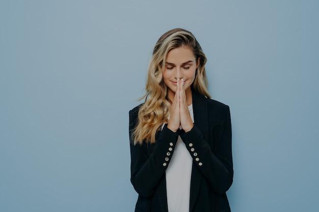 祈りのポーズで立っている美しい若いブロンドの女の子は、目を閉じて手のひらを折りたたんで、嘆願し、願いを叶え、コピースペースのある青いスタジオの背景に隔離されています