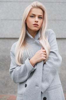Beautiful young blond hair woman in grey coat