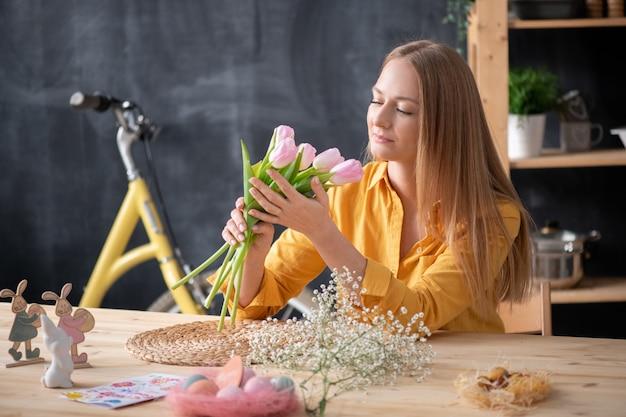 イースターの装飾とチューリップの香りでテーブルに座っている美しい若いブロンドの髪の女性