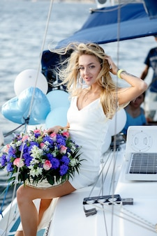 Beautiful young blond woman in a dress on a yacht