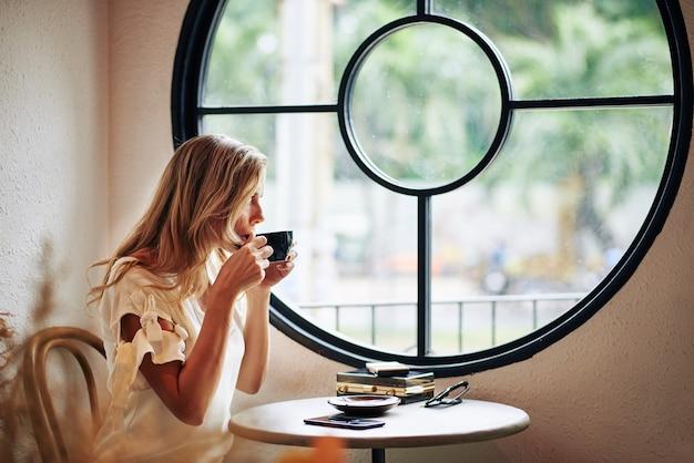 Красивая молодая блондинка женщина пьет чашку капучино и смотрит через окно кафе