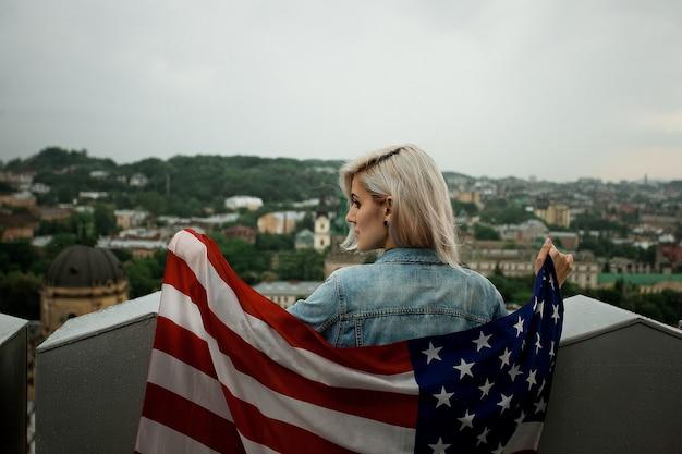 Красивая молодая белокурая женщина на пространстве города с американским флагом