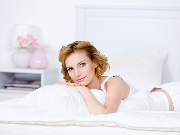 Красивая молодая блондинка женщина расслабляющий на кровати дома