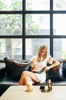 Beautiful young blond woman sitting on leather sofa, drinking sweet refreshing cocktail and writing journal